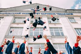 Hand throwing student hats in the air